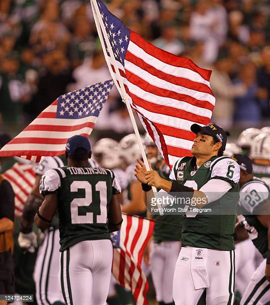 Jets quarterback Mark Sanchez carries the American flag before the start of New Yorks game against the Dallas Cowboys in East Rutherford New Jersey...