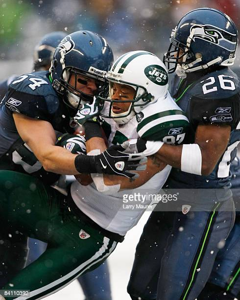 Jets wide receiver Laveranues Coles is tackled after a catch by Seahawks cornerback Josh Wilson and linebacker Will herring during the game between...