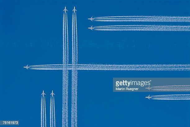 jets with vapour trails in blue sky, view from below (digital composite) - rangschikken stockfoto's en -beelden