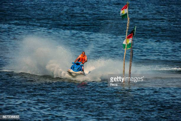 Jetski around a post holding two flags of Kurdistan on the lake Dukan near the town of RanyaThe soils are fertile cultivated and well irrigated...