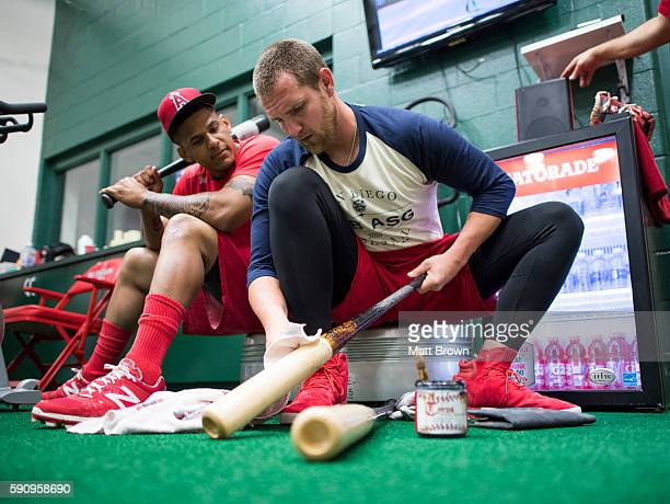 Jett Bandy of the Los Angeles Angels of Anaheim applies pine tar his bat while talking to Jefry Marte in the clubhouse batting cage before the game...