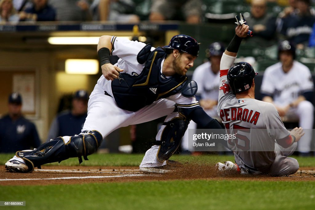 Jett Bandy #47 of the Milwaukee Brewers tags out Dustin Pedroia #15 of the Boston Red Sox at home plate in the first inning at Miller Park on May 10, 2017 in Milwaukee, Wisconsin.
