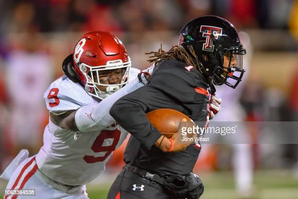 Jett Duffey of the Texas Tech Red Raiders tries to break the tackle of Kenneth Murray of the Oklahoma Sooners during the game on November 3 2018 at...