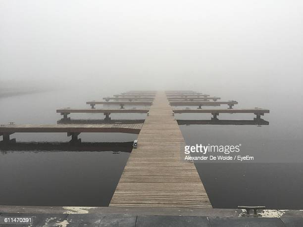 Jetties In Lake During Foggy Weather