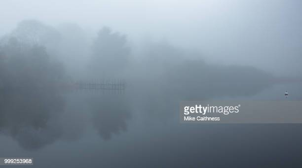 jetty and buoy in the mist - mike caithness stock pictures, royalty-free photos & images