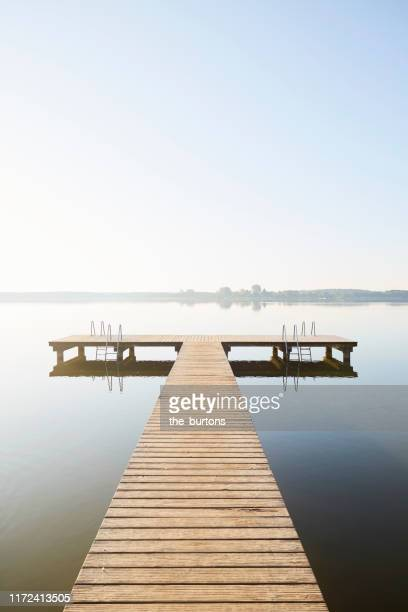 jetty at an idyllic lake with smooth water in the morning against claer sky, tranquil scene - tranquil scene photos et images de collection