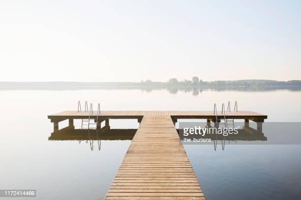 jetty at an idyllic lake with smooth water in the morning against claer sky, tranquil scene - jetty stock pictures, royalty-free photos & images