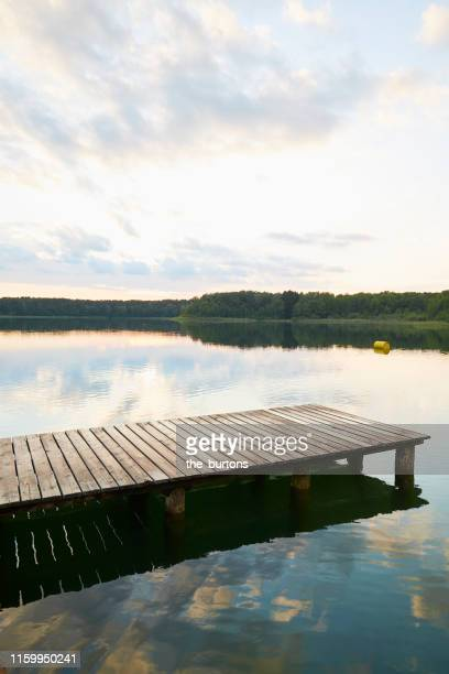jetty at idyllic lake during sunset, clouds are reflected in the water - embarcadero fotografías e imágenes de stock