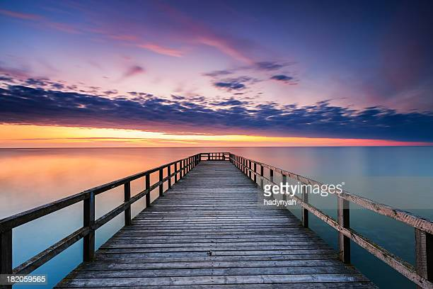 jetty at sunset - pier stock pictures, royalty-free photos & images