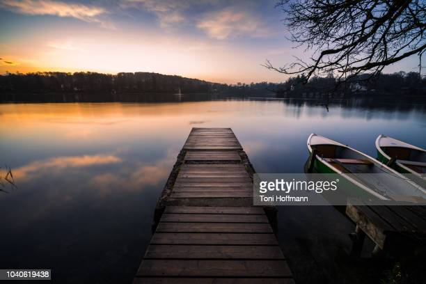 jetty at wesslinger see with some boats at sunrise - naturwunder stock-fotos und bilder