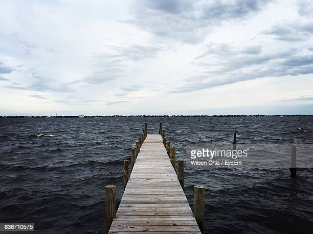 Jetty In Sea Against Cloudy Sky