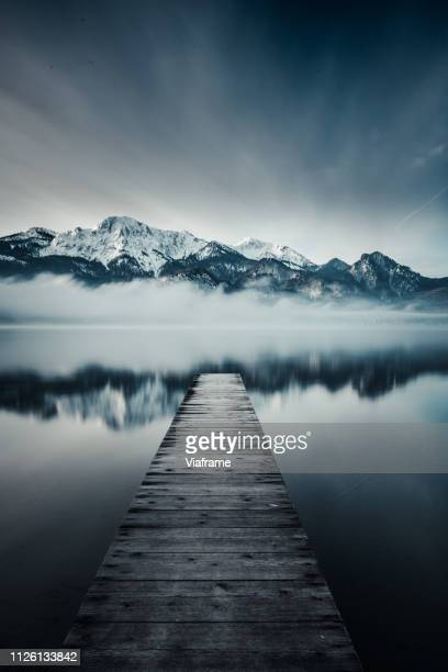 jetty leading towards mountain range - jetty stock pictures, royalty-free photos & images