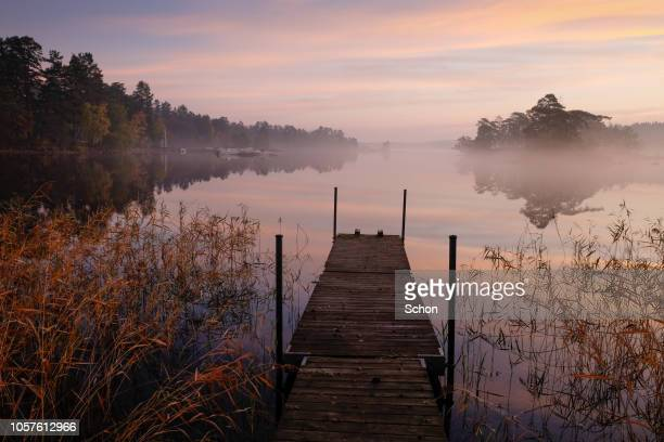 jetty on a quiet lake with islands and boats in the background a fall morning - riva del lago foto e immagini stock