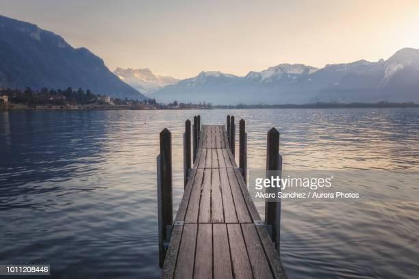 jetty on shore of lake geneva, switzerland - meer van genève stockfoto's en -beelden