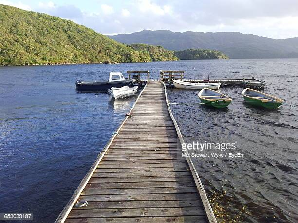 Jetty With Moored Boats Leading To Calm Sea