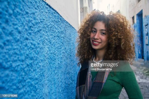 jeune femme avec cheveux bouclés souriante - north africa stock pictures, royalty-free photos & images