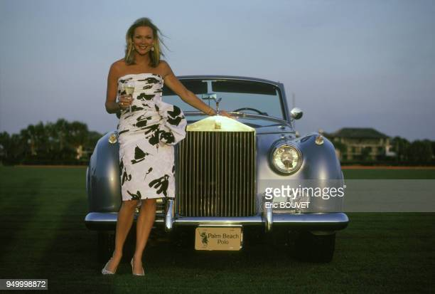 Jeune femme avec une coupe de champagne à la main et Rolls-Royce lors d'une compétition de polo en Floride en mars 1986, Etats-Unis.