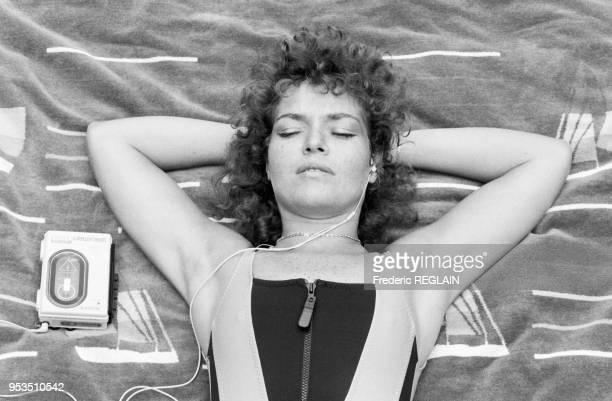 Jeune femme écoutant de la musique avec son Walkman à Paris en juillet 1988, France.