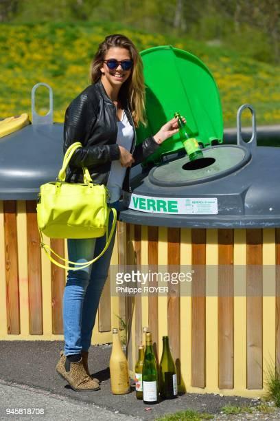 Jeune femme de 18 ans triant ses dechets et jetant du verre dans une poubelle MR