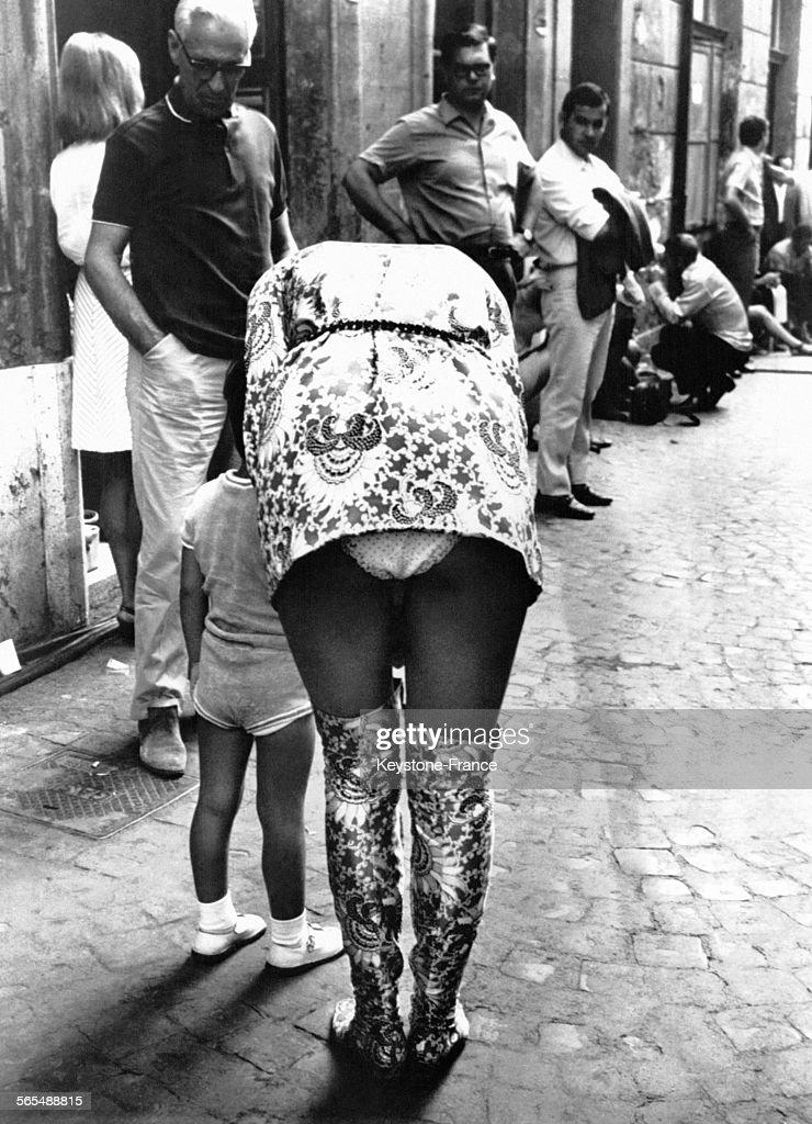 Jeune femme en minijupe se penchant vers son enfant à Milan Italie le 3  octobre 1968