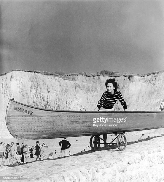 Jeune femme portant un pull marinière avec son canoé sur les plages de Normandie France circa 1940