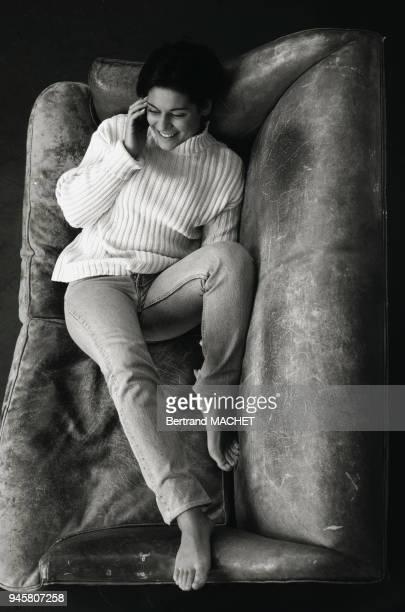 Jeune femme tlphonant allonge sur un canap