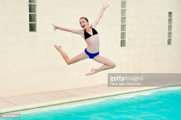 Jeune fille sautant dans une piscine
