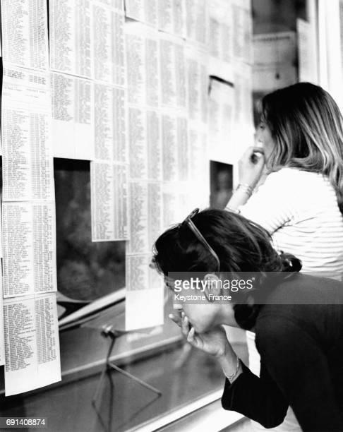 Jeune lycéenne cherchant son nom dans la liste des reçus au baccalauréat, à Perpignan, France, en juillet 1965.