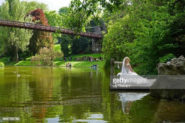 Jeune mariée posant pour la photo dans le parc des Buttes Chaumont au printemps 24 avril 2017 Paris 19ème France