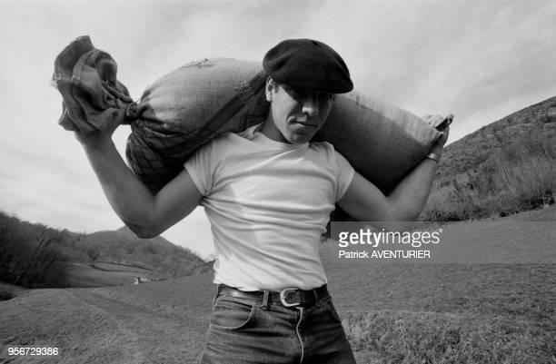 Jeune paysan basque portant un sac de sable lors de jeux de forces aux PaysBasque en février 1987 France