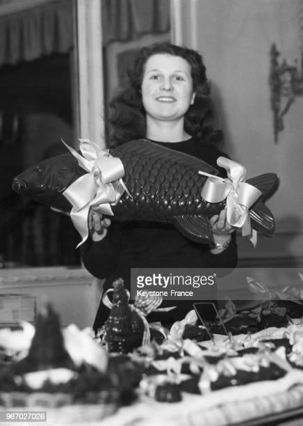 Jeune vendeuse présentant un gros poisson en chocolat pour Pâques à Paris en France le 31 mars 1950