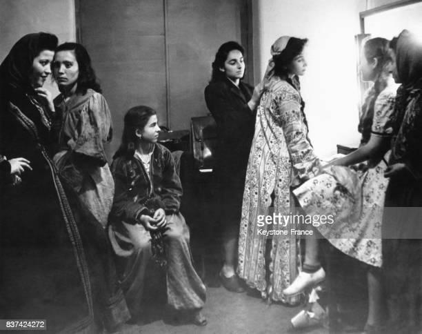 Jeunes actrices de la troupes d'amateurs du 'Théâtre du Peuple' dans leur loge avant d'entrer en scène à droite de profil la vedette de la troupe...
