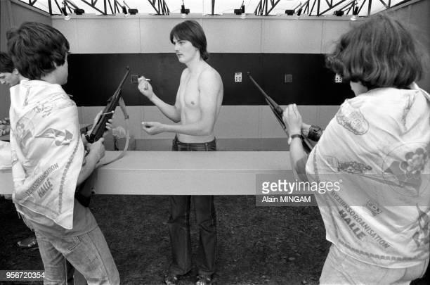 Jeunes allemands tirant à la carabines dans une fête foraine lors des manifestations célébrant le 30ème anniversaire de la fondation de la RDA à...