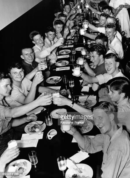 Jeunes cheminots portant un toast avec des verres de lait pour féliciter leurs formateurs et célébrer la fin de leur stage le 25 juin 1944 à...