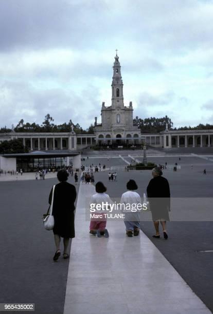 Jeunes croyantes avançant sur les genoux sur la place devant le sanctuaire de Fatima à Fatima Portugal