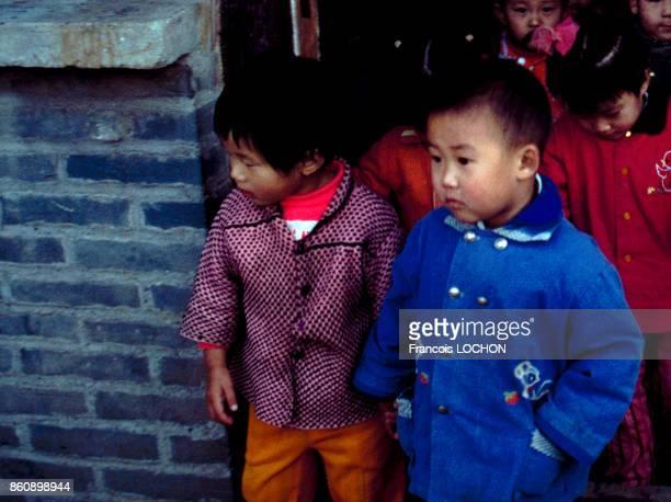 Jeunes enfants sortant d'une école maternelle en octobre 1980 à Pékin Chine