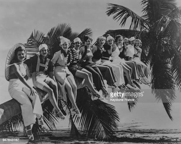 Jeunes femmes assises sur une branche de palmier sur une plage de Californie aux EtatsUnis en 1934
