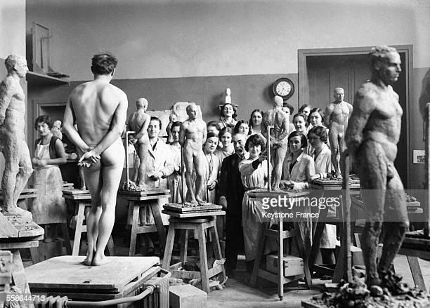 Jeunes femmes devant un homme nu dans un cours de sculpture à Paris France en février 1930