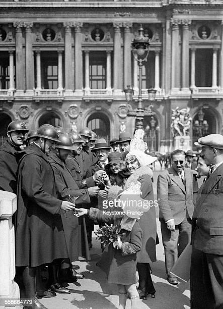Jeunes femmes offrant des brins de muguet à des policiers déployés dans les rues de Paris France le 1 mai 1931