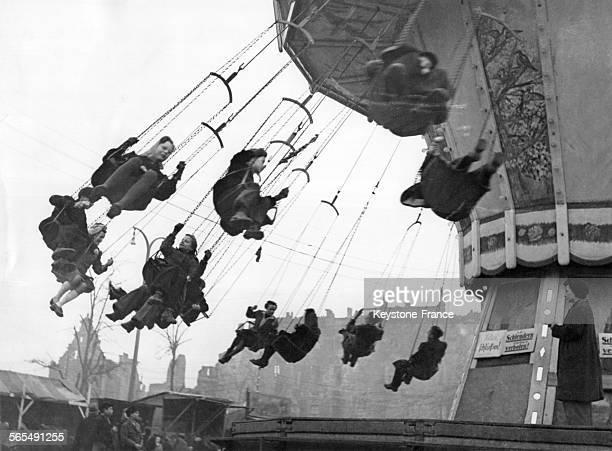 Jeunes filles et garçons suspendus aux chaînes d'un manège à une fête foraine devant les maisons détruites par la guerre à Berlin Allemagne circa 1940