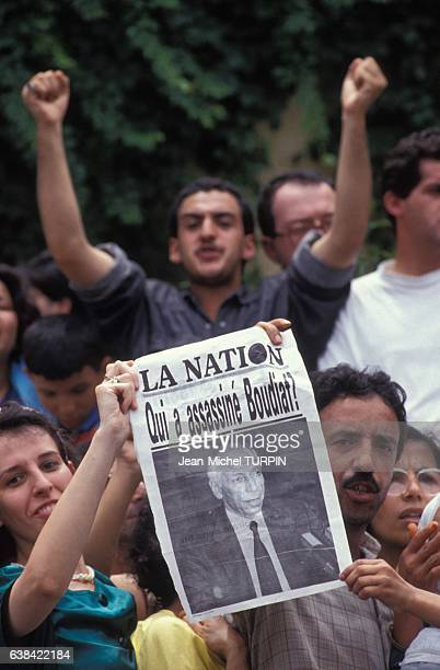 Jeunes gens montrant la une du quotidien 'La Nation' lors des obsèques de Mohamed Boudiaf le chef de l'Etat algérien assassiné le 1er juillet 1992 à...