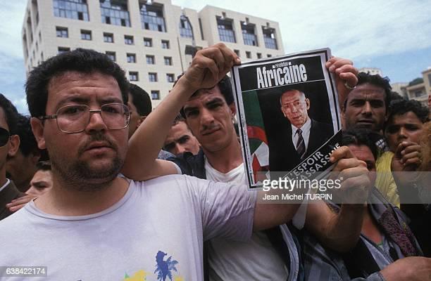 Jeunes gens montrant un portrait de Mohamed Boudiaf lors des obsèques du chef de l'Etat assassinè le 1er juillet 1992 à Alger Algérie