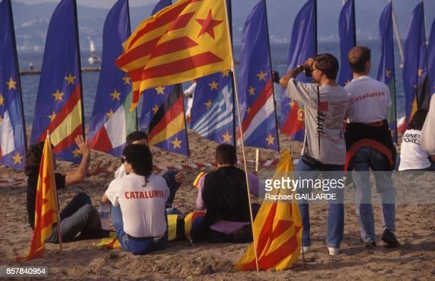 Jeunes gens sur une plage entoures de drapeaux europeens et catalans en juin 1992 a Barcelone Espagne