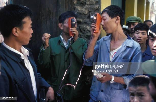 Jeunes hommes regardant un film court au moyen d'un petit projecteur de cinéma contenu dans un boitier individuel payant en août 1980 à Kunming Chine