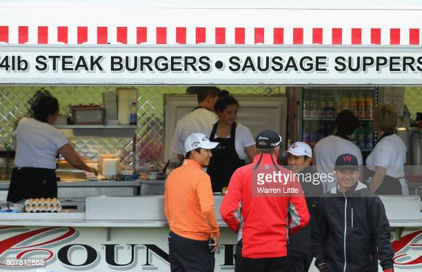 Jeunghun Wang and Soomin Lee of Korea buy a burger during a practice round ahead of the Dubai Duty Free Irish Open at Portstewart Golf Club on July 4...