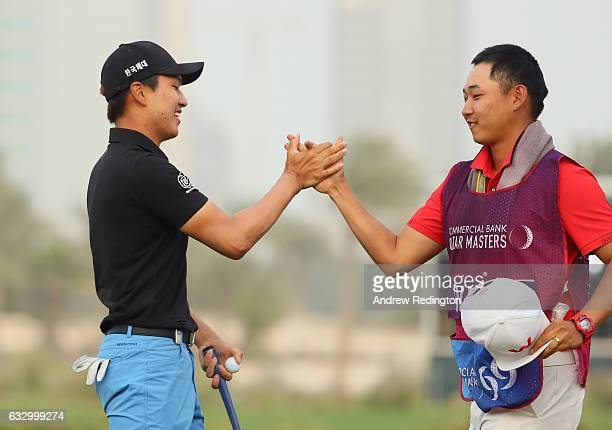 Jeunghun Wang of South Korea celebrates his victory in the playoff with caddie Dongwoo Ko during the fourth round of the Commercial Bank Qatar...