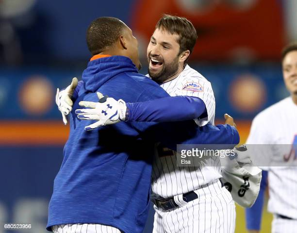 Jeurys Familia of the New York Mets congratulates Neil Walker after Walker drove in the game winning run against the San Francisco Giants on May 8...