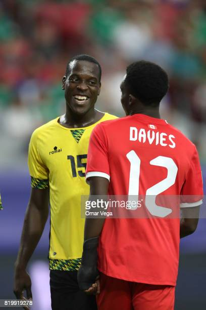 JeVaughn Watson of Jamaica talks with Alphonso Davies of Canada during the CONCACAF Gold Cup Quarterfinal match between Jamaica and Canada at...