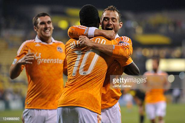 JeVaughn Watson of the Houston Dynamo is congratulated by teammate Brad Davis of the Houston Dynamo after scoring a goal against the Columbus Crew in...