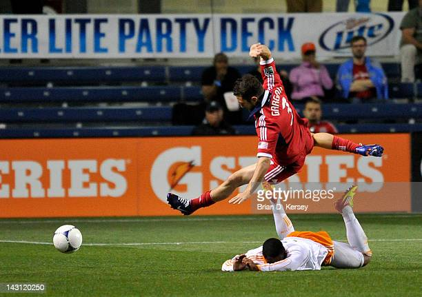 JeVaughn Watson of the Houston Dynamo trips up Dan Gargan of the Chicago Fire at Toyota Park on April 15 2012 in Bridgeview Illinois The Fire and...